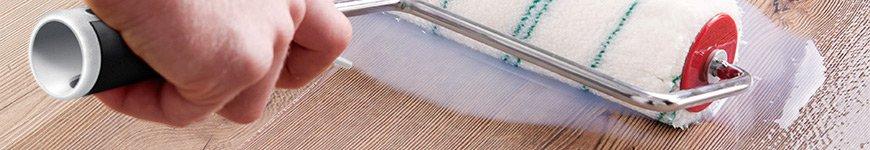 Un Proschutz dépose une couche de protecteur PU au rouleau sur un sol.