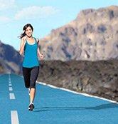 Une jeune femme court sur une route avec du bitume de couleur bleu. Elle se rend à une formation Dr. Schutz à Étroussat !