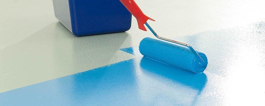 Un rouleau posé sur le sol en train de passer une couche de PU Color bleu