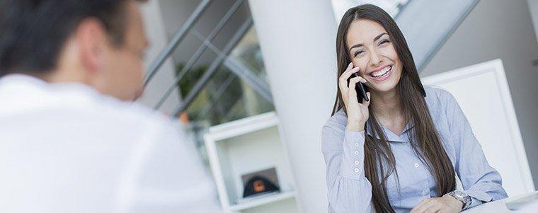 Une architecte souriante au téléphone en train de discuter avec Dominique Vichy à propos du sol incroyable réalisé dans son dernier projet de rénovation immobilière.