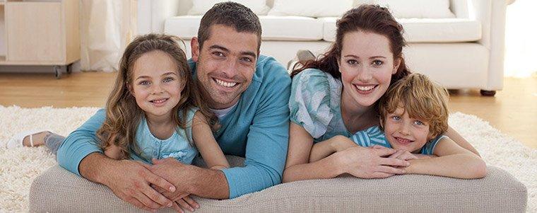 Une famille heureuse avec deux parents et deux enfants, allongés sur le tapis de leur salon.