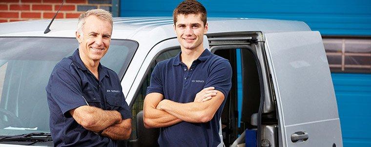Deux applicateurs Dr. Schuts en tenue de travail devant une voiture de la société