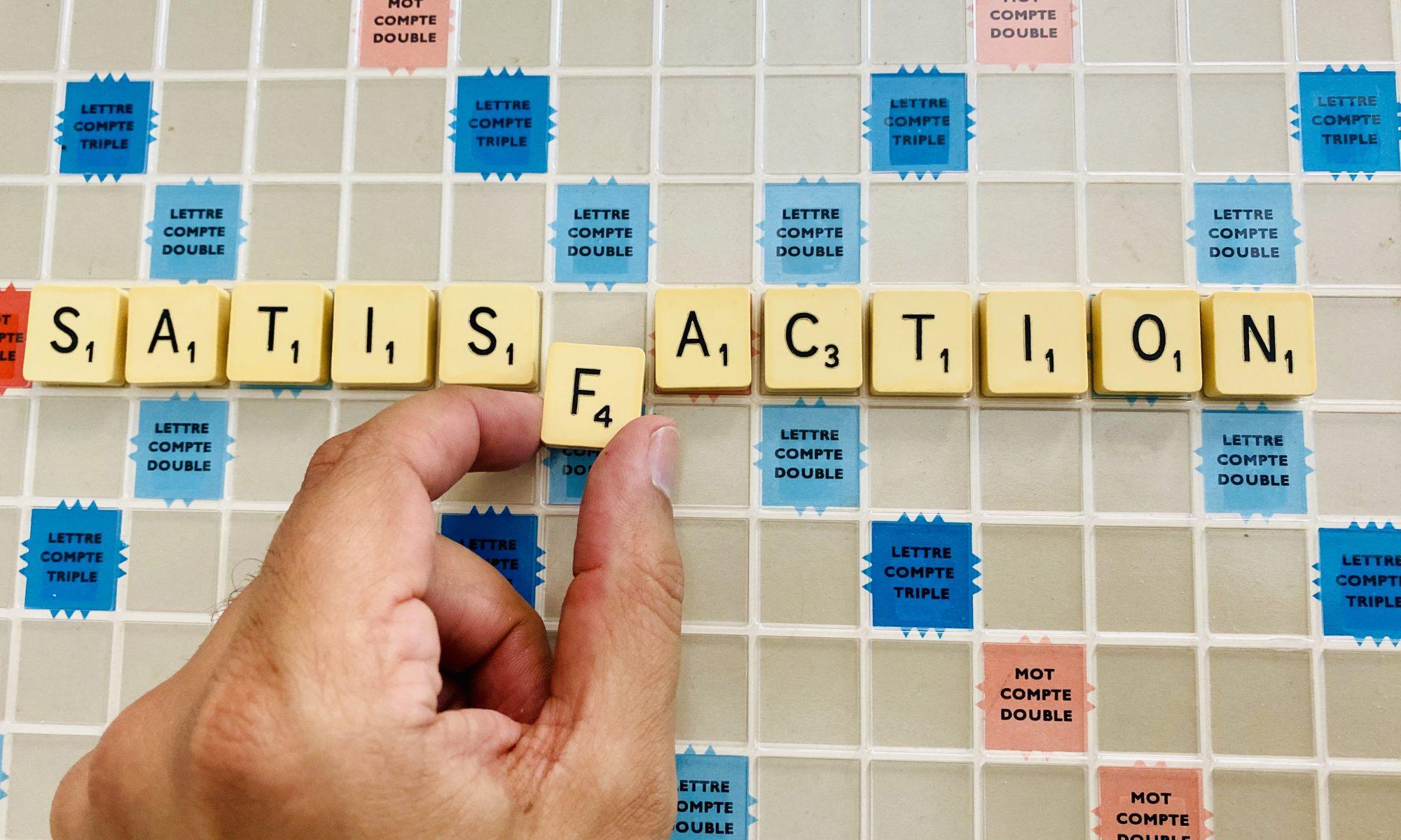 """Le mot """"satisfaction"""" inscrit sur un plateau de Scrabble"""
